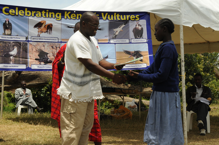 Dr Erustus Kanga of Kenya Wildlife Services presents a prize to one of the winners of the Vulture art competition.